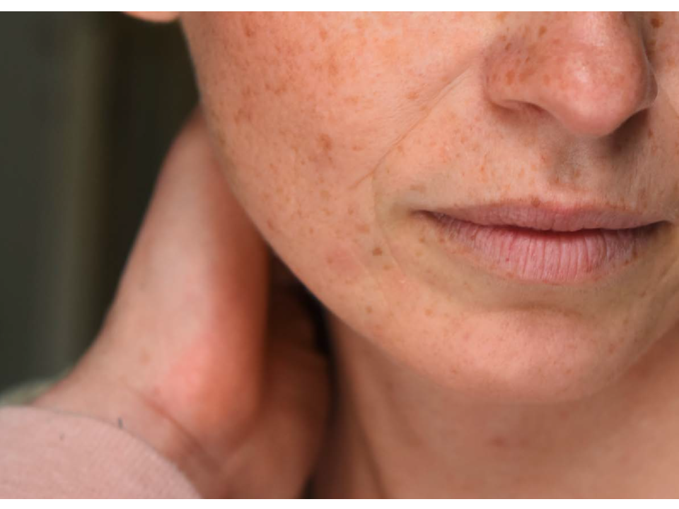 Close up image of the lower half of a woman's face and hand